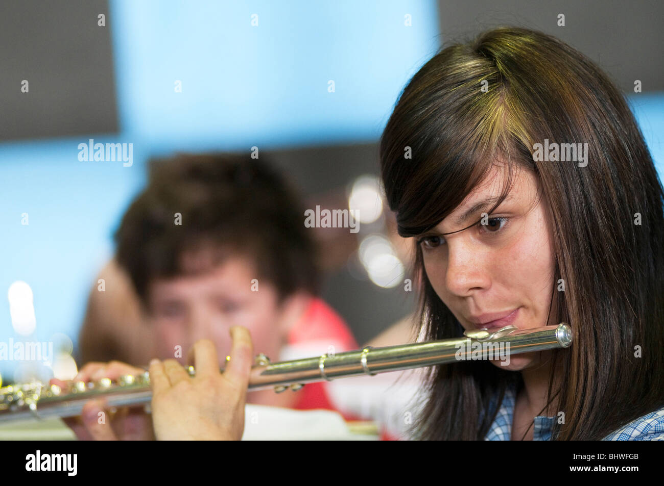 A young girl playing flute in a high school orchestra - Stock Image