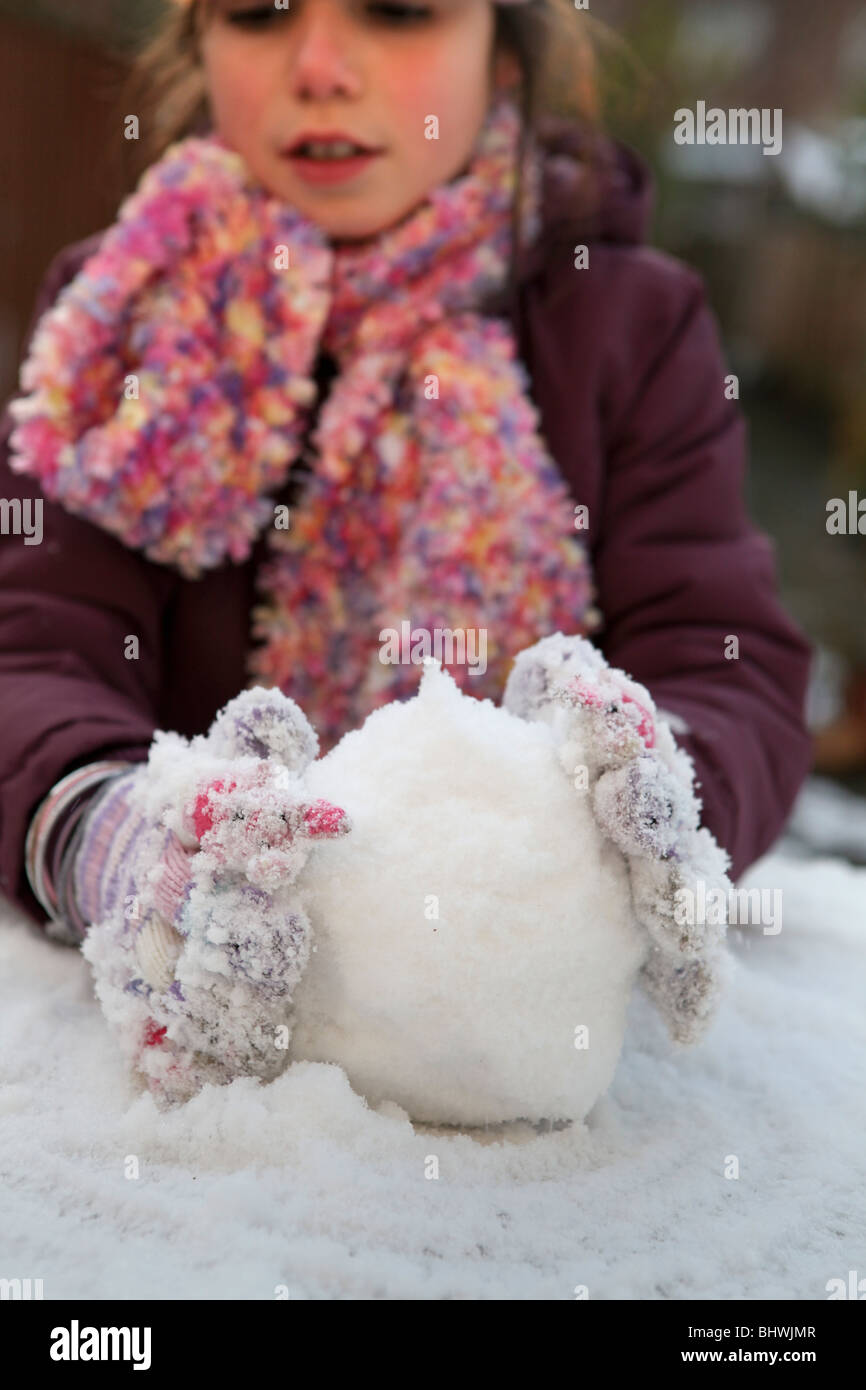 Child playing with snowball - Stock Image
