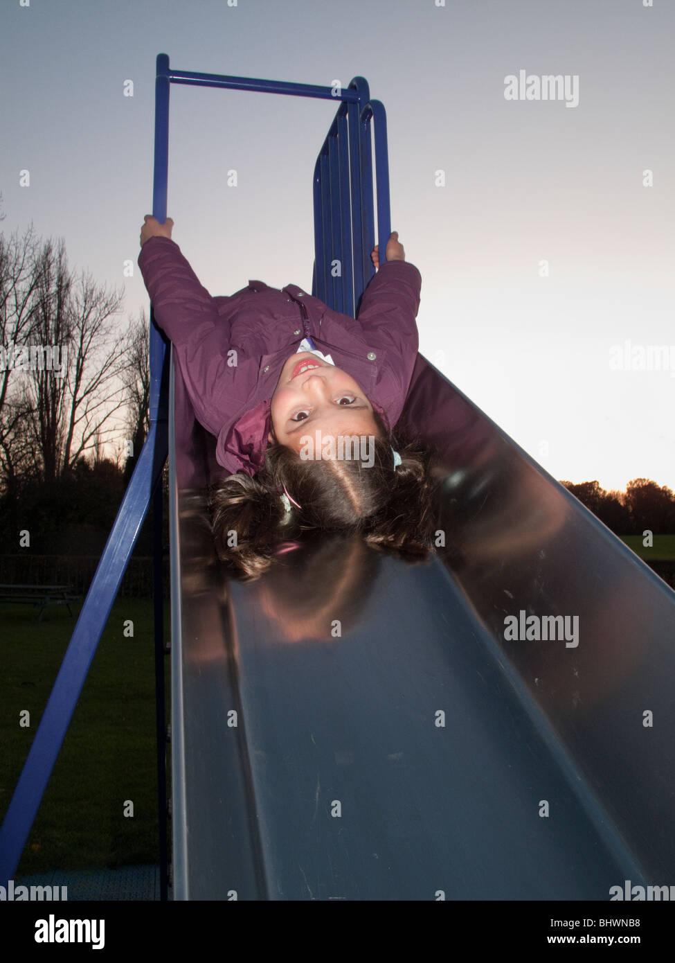 child on a playground slide - Stock Image