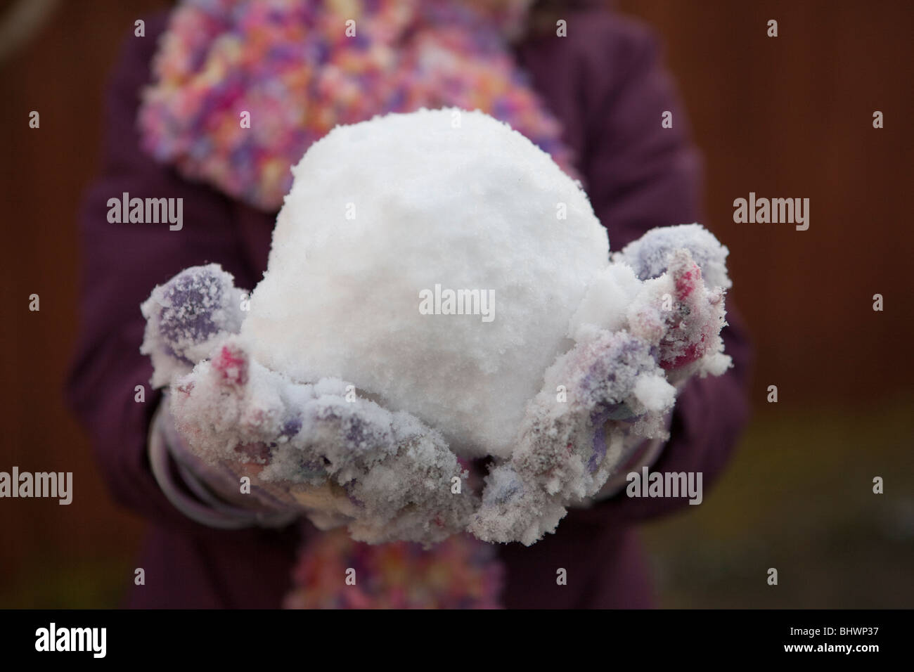 child holding a snowball - Stock Image