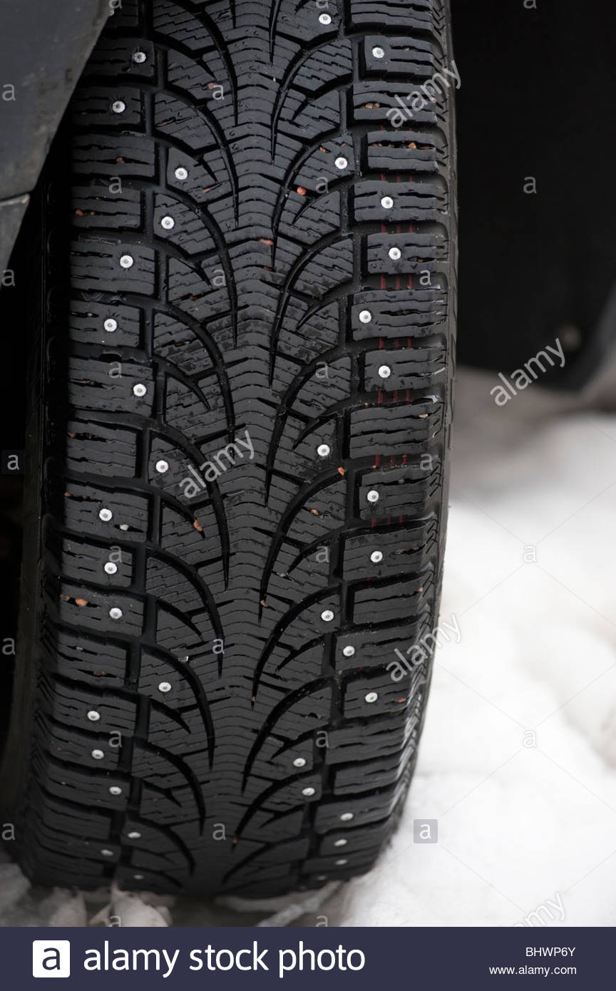 Detail of studded winter tyre on car in Sweden - it is the law to fit studded tyres during winter in Sweden - Stock Image