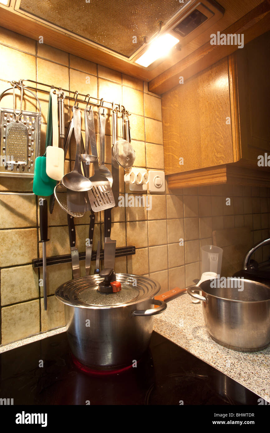 A pot of boiling water sits on a ceramic burner, clutter of kitchen utensils behind stove by Charles Lupica - Stock Image