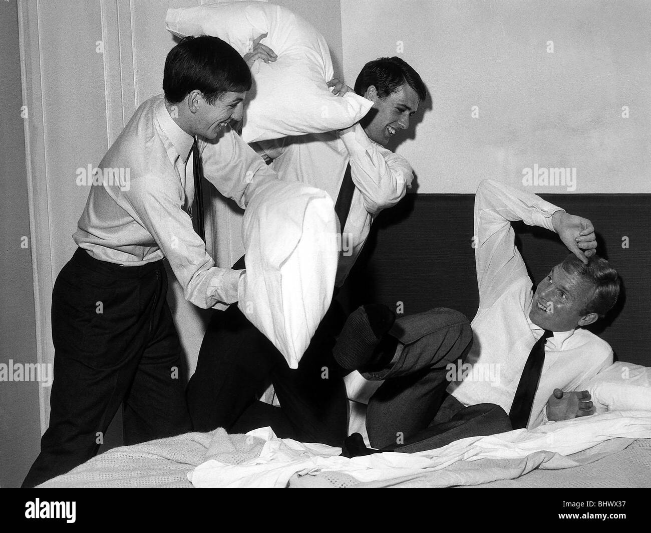 England captain Bobby Moore gets a wake-up call from West Ham and England team mates Geoff Hurst and Martin Peters - Stock Image