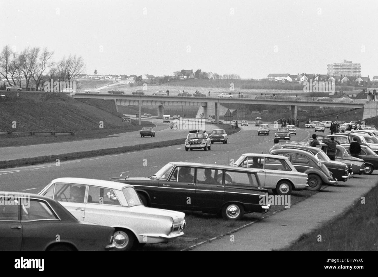 Spectators line the motorway to watch competitors in the 1970 Daily Mirrors World Cup Rally. No 3 Peter Jopp B.L.M.C. - Stock Image
