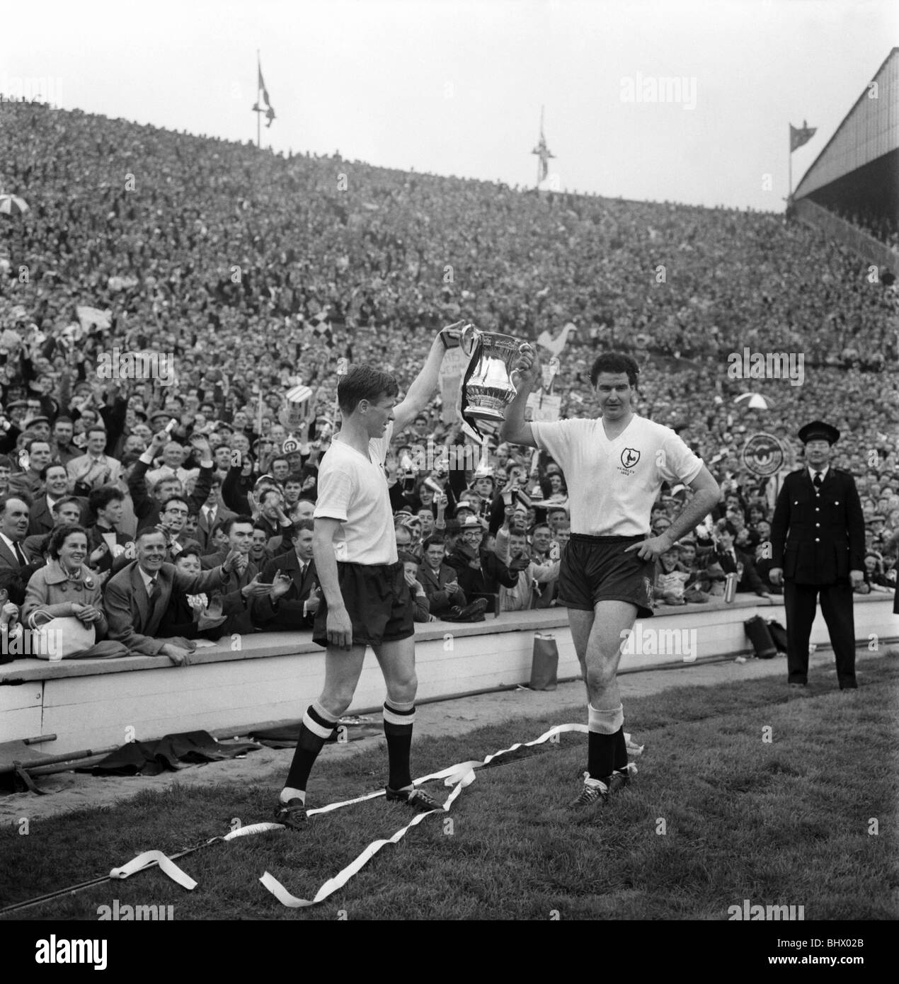 FA Cup final at Wembley Stadium. Tottenham Hotspur 3 v. Burnley 1. Maurice Norman of Spurs (right) holds up the - Stock Image