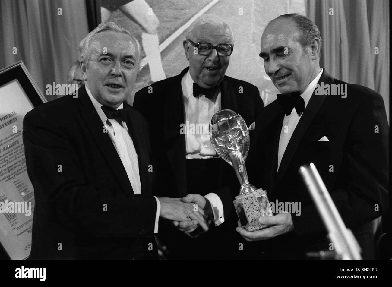 Sir Alf Ramsey holds World Cup at Cafe Royal July 1974 and shakes hands with Prime Minister Harold Wilson watched - Stock Image