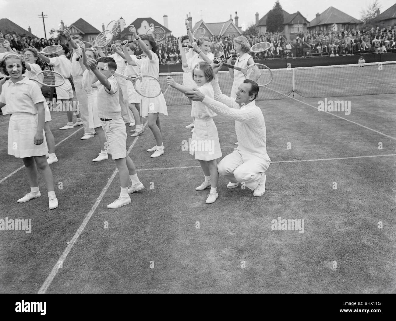 Tennis Fred Perry coaches children from the Surbiton High School.  1949 019090/1 - Stock Image