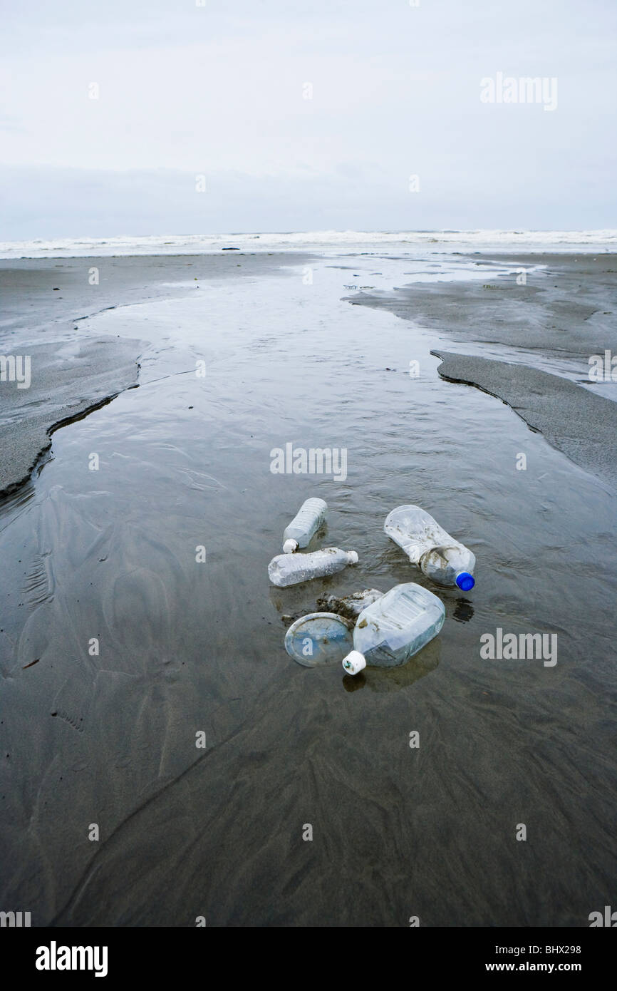 Plastic bottles and lids sitting in a stream as it flows out to the Pacific Ocean. - Stock Image