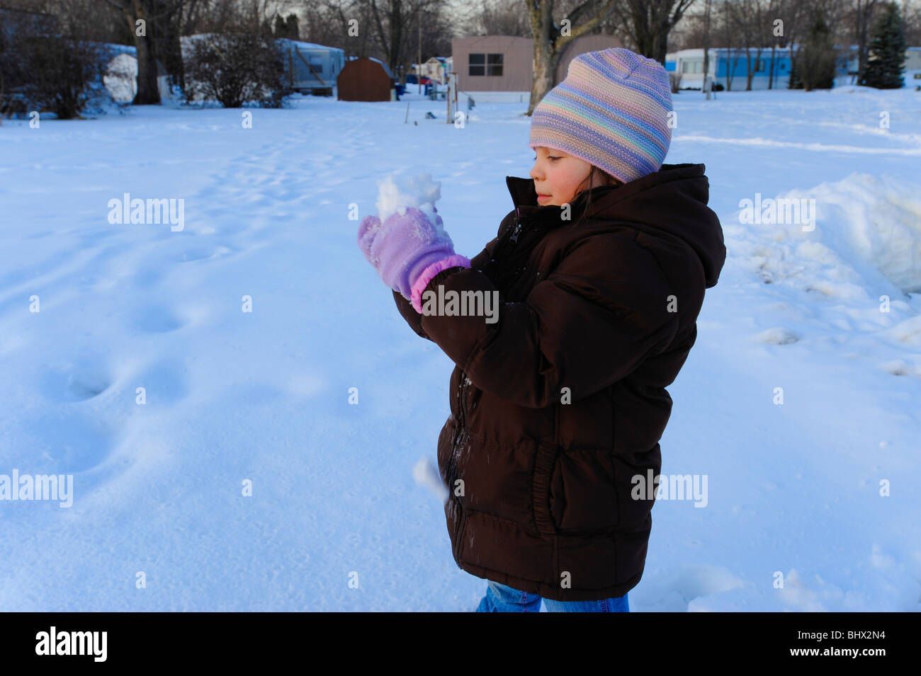 7 year old girl making snowball - Stock Image