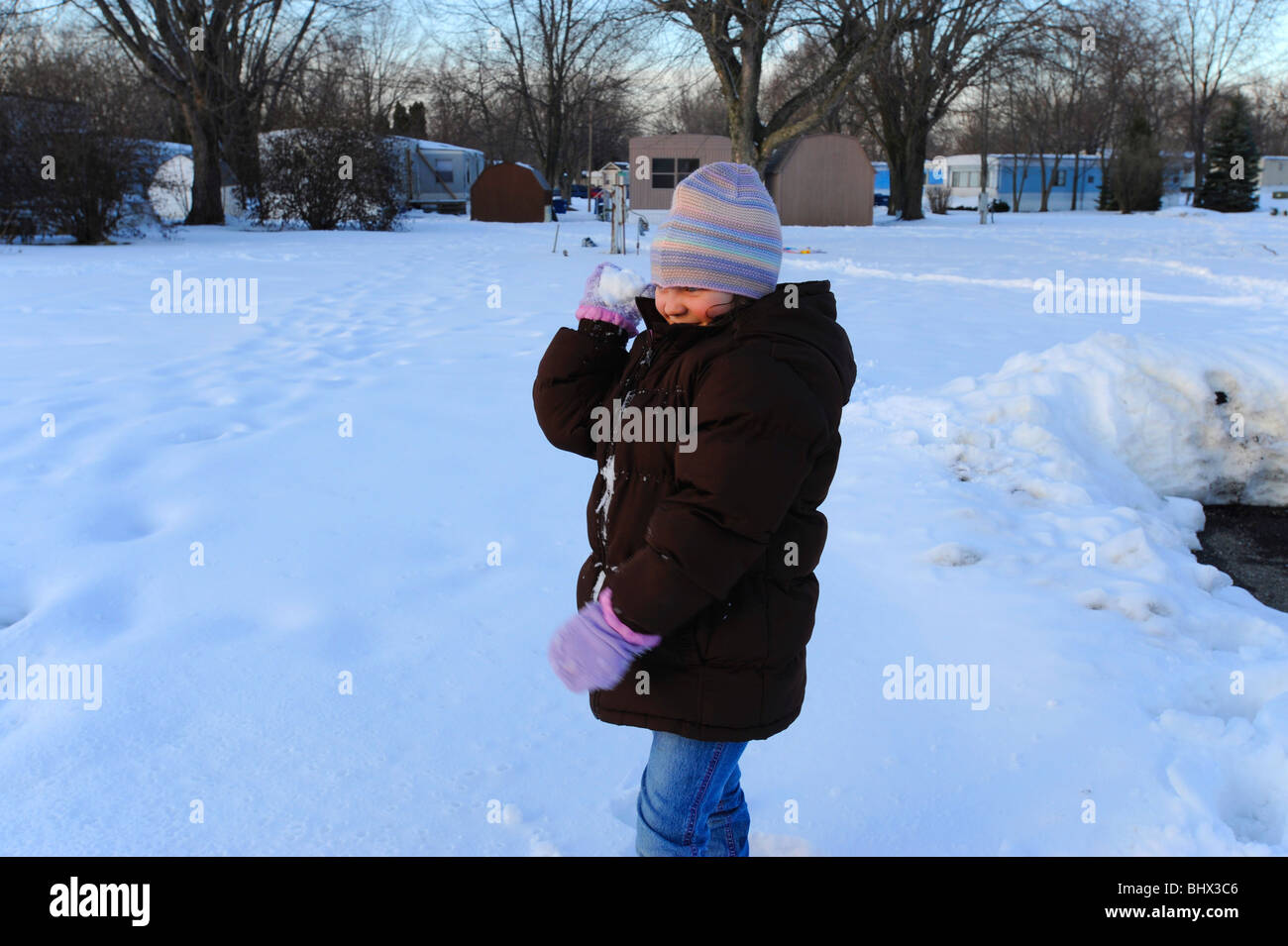 7 year old girl making and throwing snowball - Stock Image