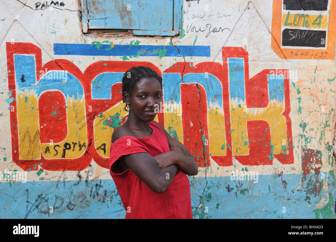 Portrait of woman outside a bank sign, Isle de la Gonave, Haiti - Stock Image
