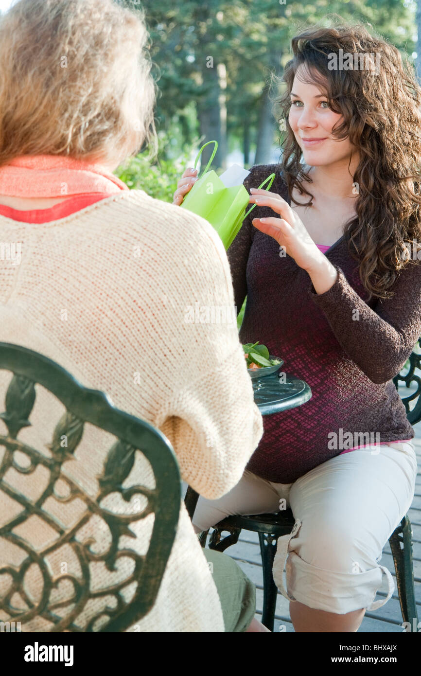 Pregnant Woman With Gift From Friend At Outdoor Table, Manitoba, Canada - Stock Image