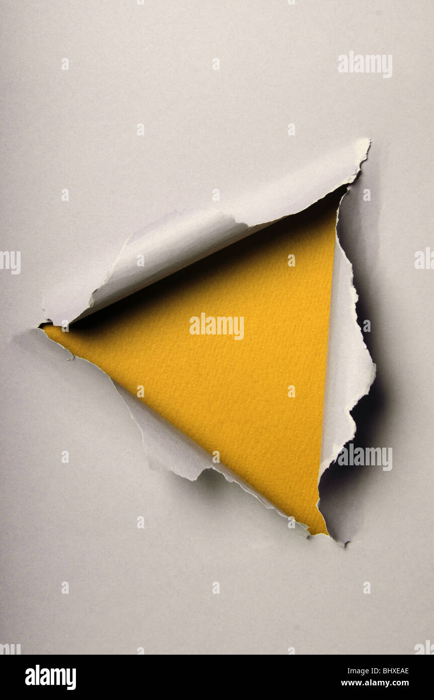 Old ripped paper forming triangle over yellow background - Stock Image
