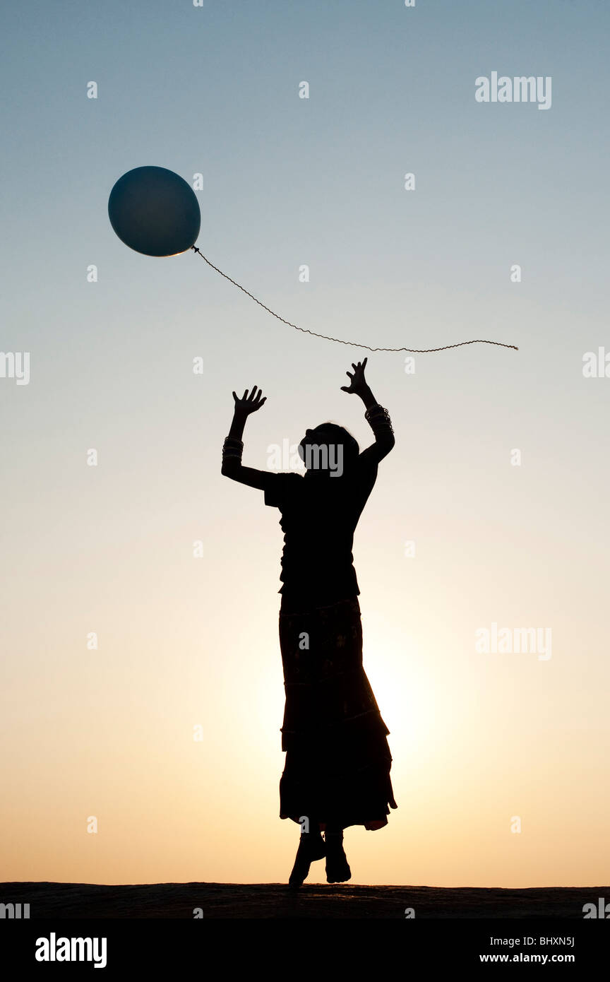 Silhouette of a young Indian girl playing with a balloon at sunset. India - Stock Image