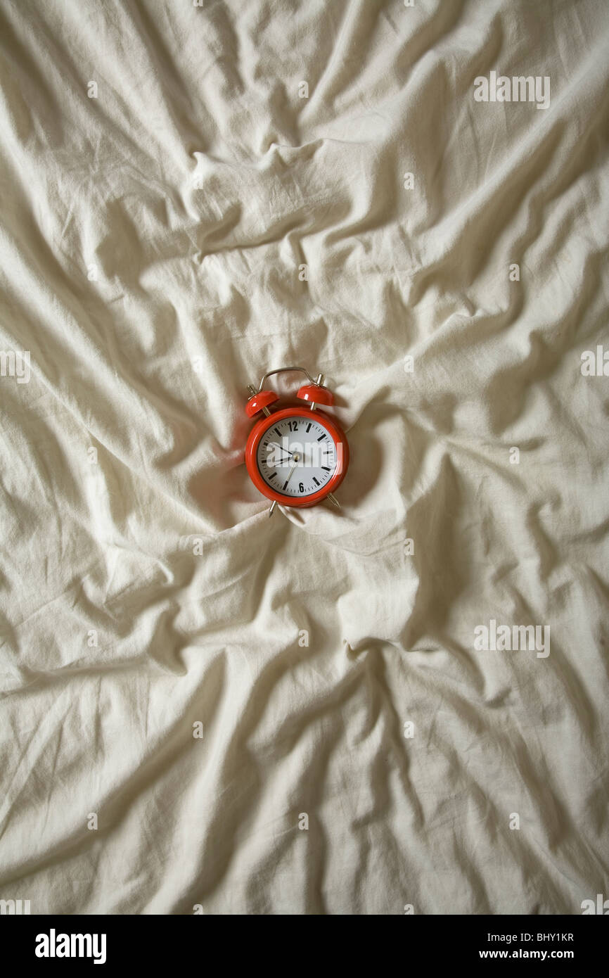 Red Alarm clock on a wrinkled duvet. Nice time, or lateness concept shot that looks good at a large size - Stock Image