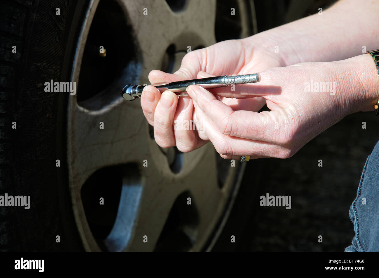 Woman car driver holding a tyre pressure gauge for checking the vehicle's tyres & pressures - Stock Image