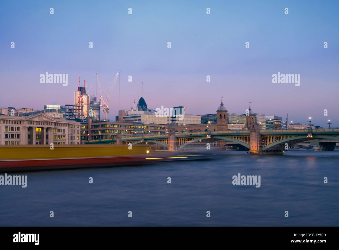 Southwark Bridge in central London looking from the South Bank at early evening with a boat traveling past leaving - Stock Image