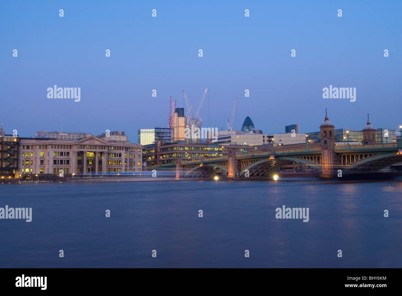 Southwark Bridge in central London looking from the South Bank at early evening with a boat travelling past leaving - Stock Image