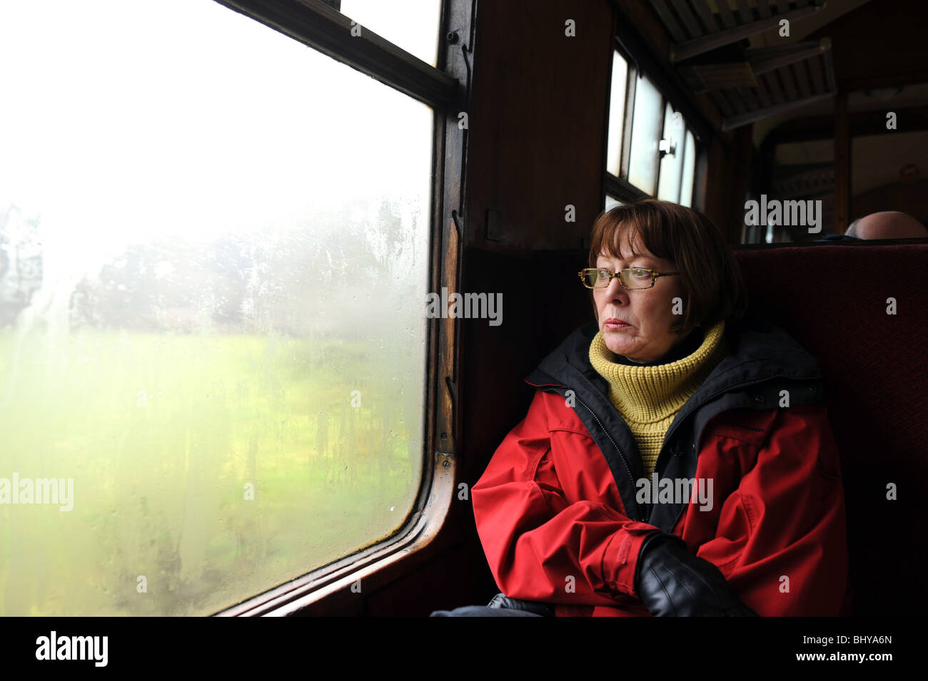 Female train passenger staring out of the window Stock Photo
