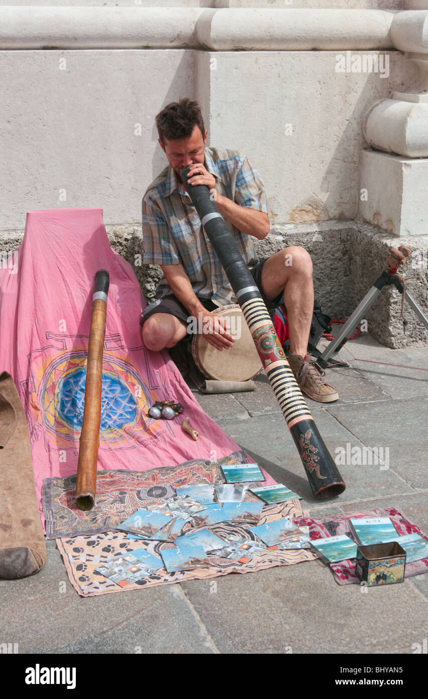 Young Caucasian male street musician playing folk music with wind instrument bamboo oboe - Stock Image