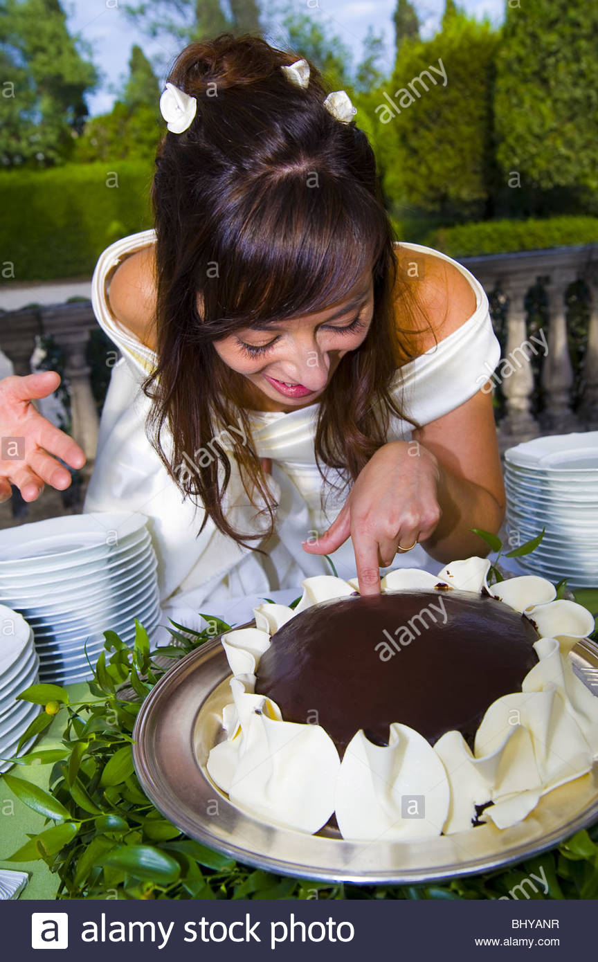 Bride putting finger in a chocolate wedding cake - Stock Image