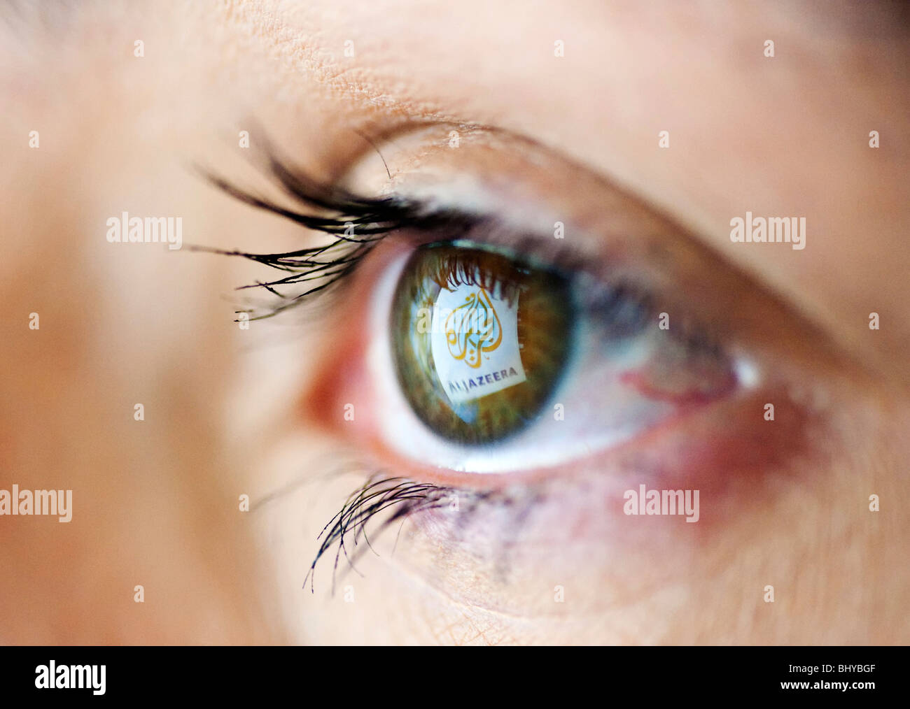Arabic television channel news service Al Jazeera website logo reflected in womans eye from computer screen - Stock Image