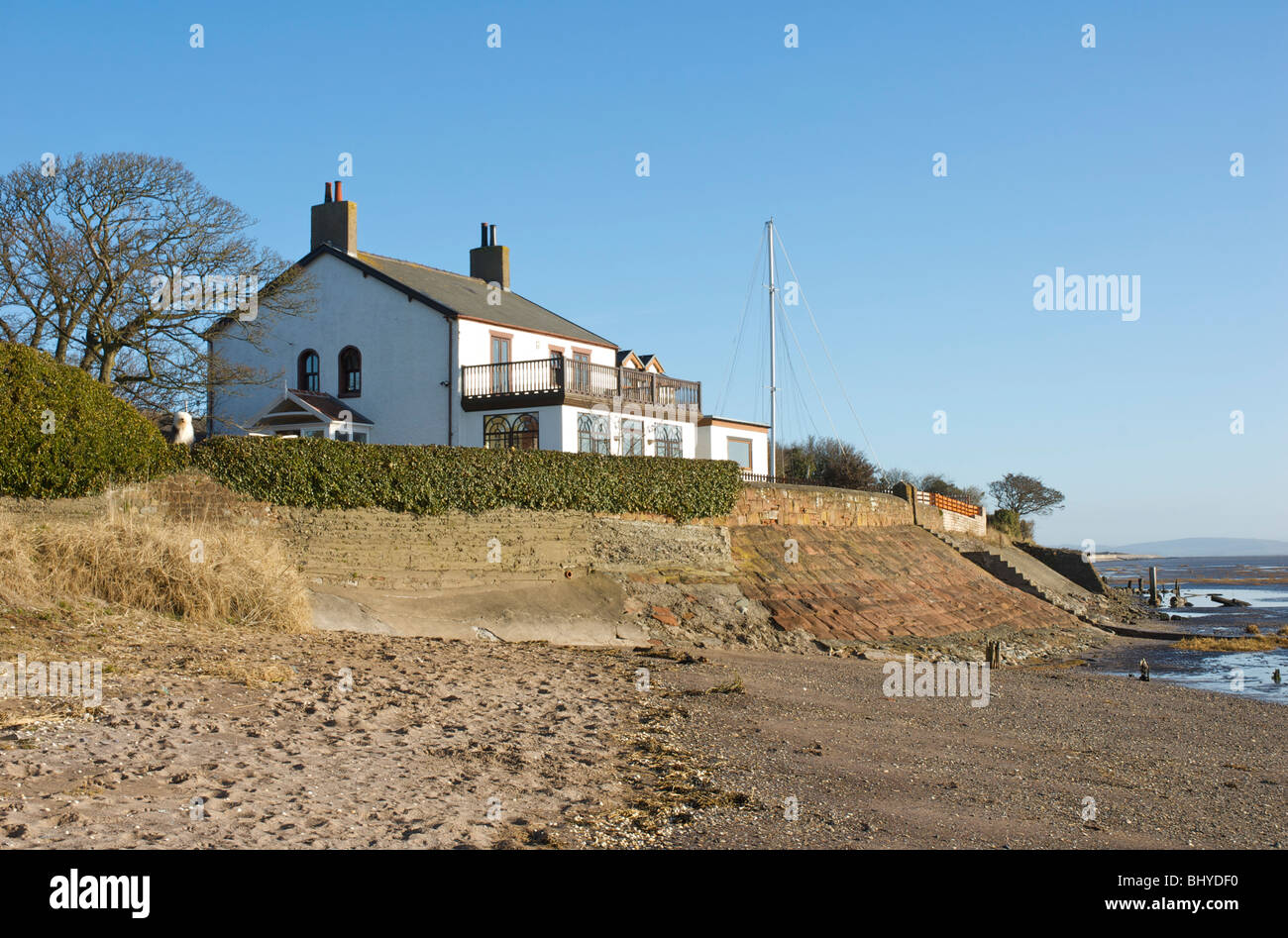 House with sea defence wall at Rampside, near Barrow-in-Furness, Cumbria, England UK - Stock Image