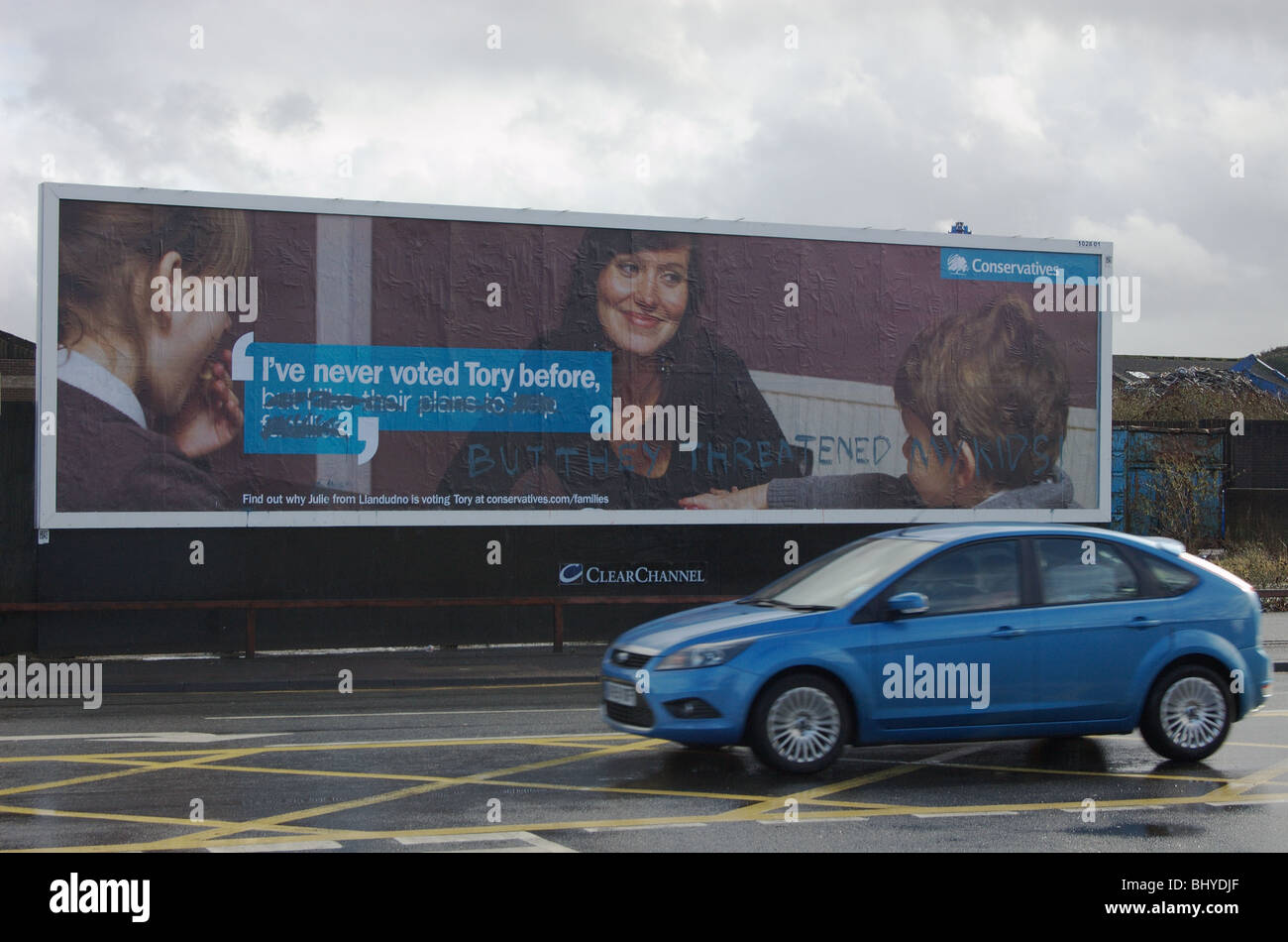 Defaced Conservative party billboard with text I've never voted Tory before BUT THEY THREATENED MY KIDS(graffiti - Stock Image