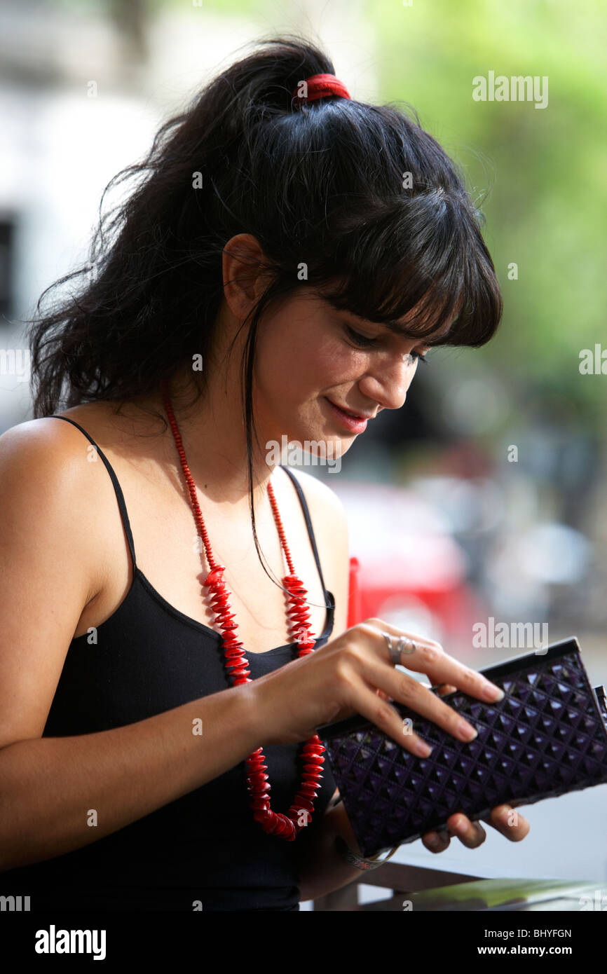 mid twenties hispanic woman checking in her purse at an outdoor cafe table - Stock Image