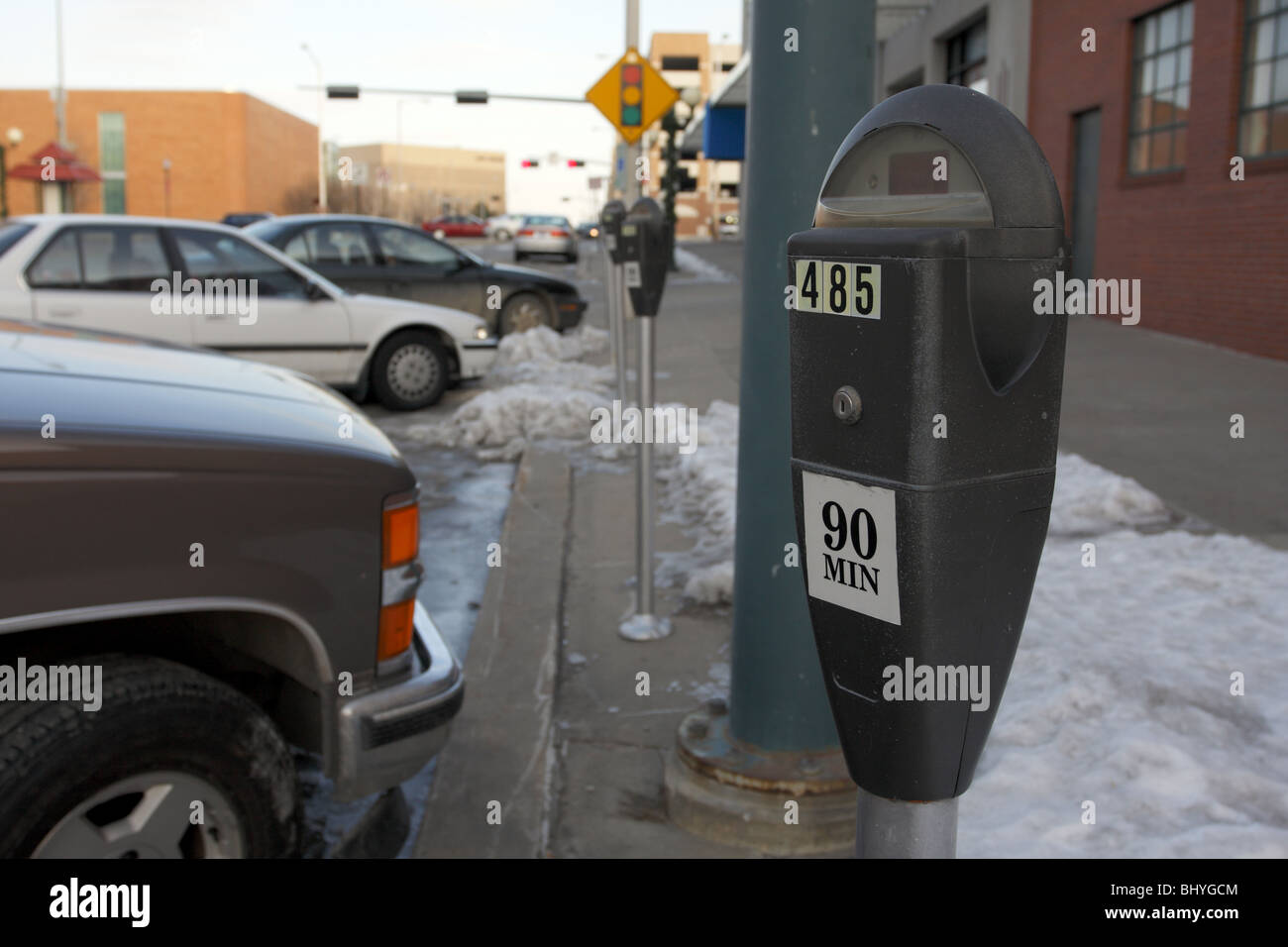 Parking meter on snowy urban street. - Stock Image