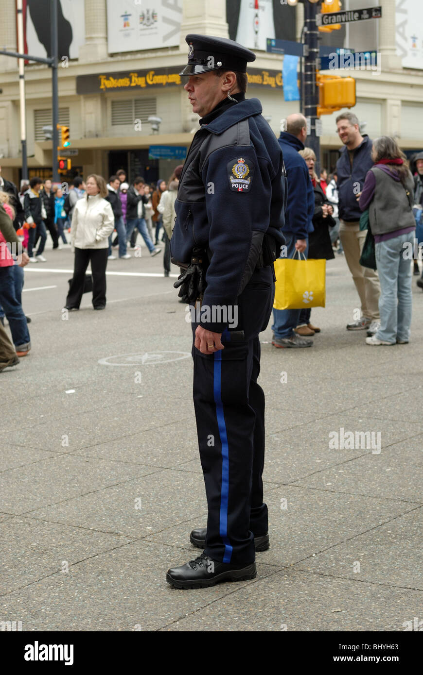 Vancouver Policeman standing on the sidewalk ensuring everyone and thing is safe. - Stock Image