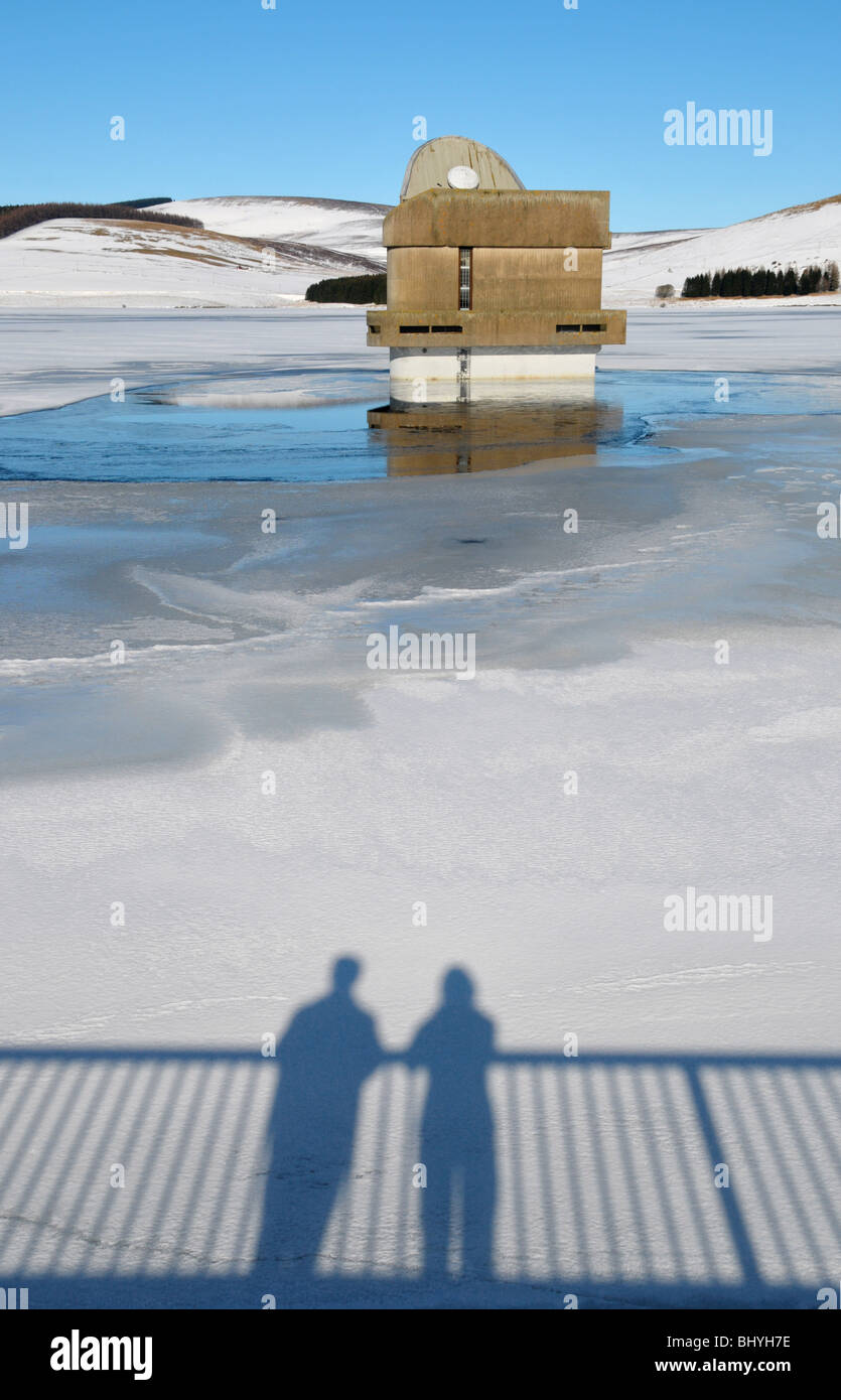 Shadowed silhouette of a couple on a snow dusted and frozen reservoir. - Stock Image