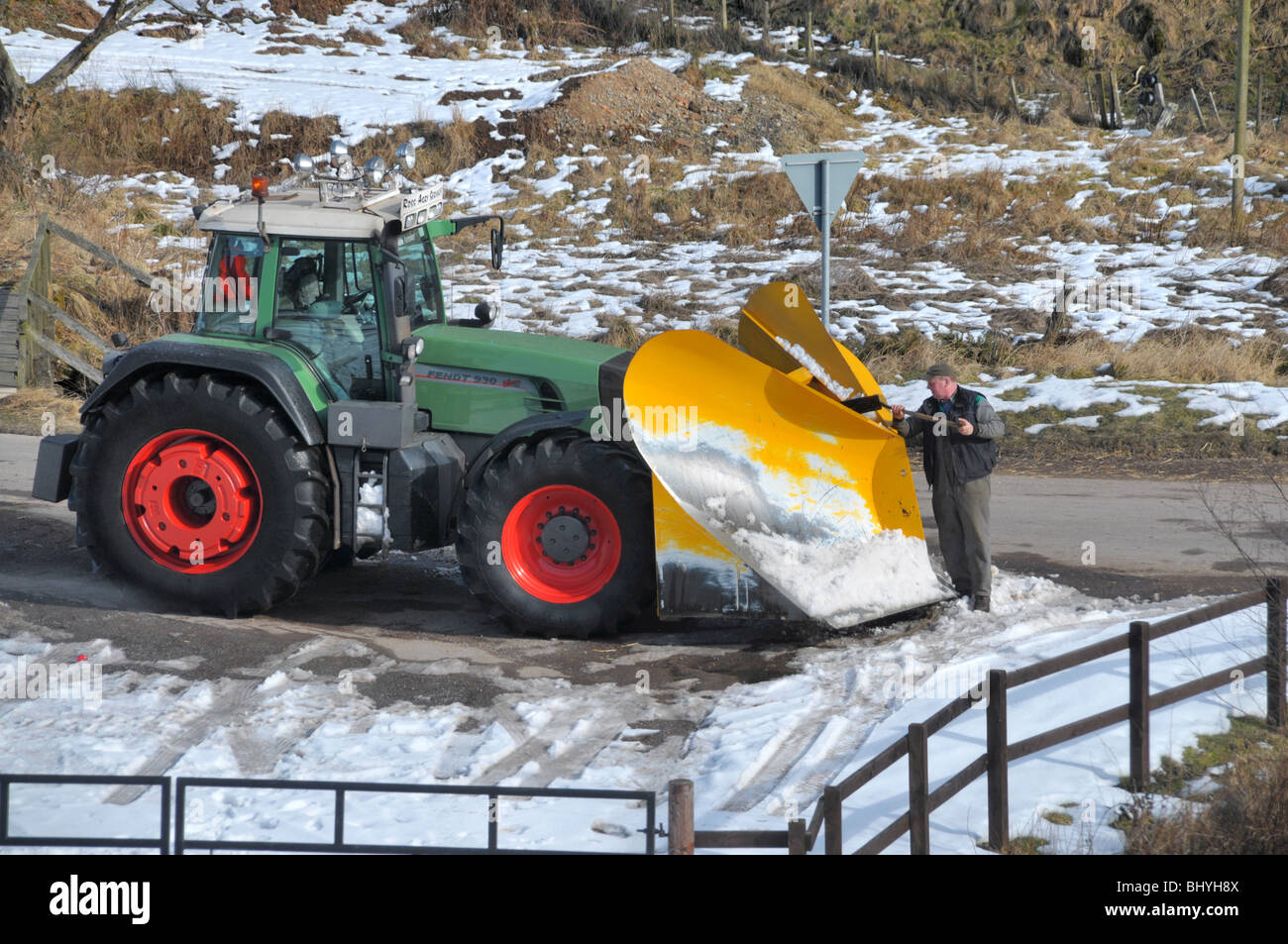 Des Moines Shopping >> A man shovels off frozen snow from a tractor snow plow ...
