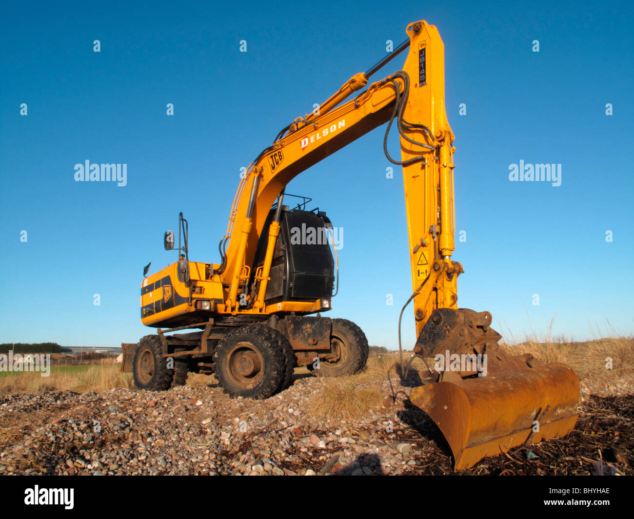 A JCB delson digger clears rubble and rocks from a collapsing river embankment. Stock Photo