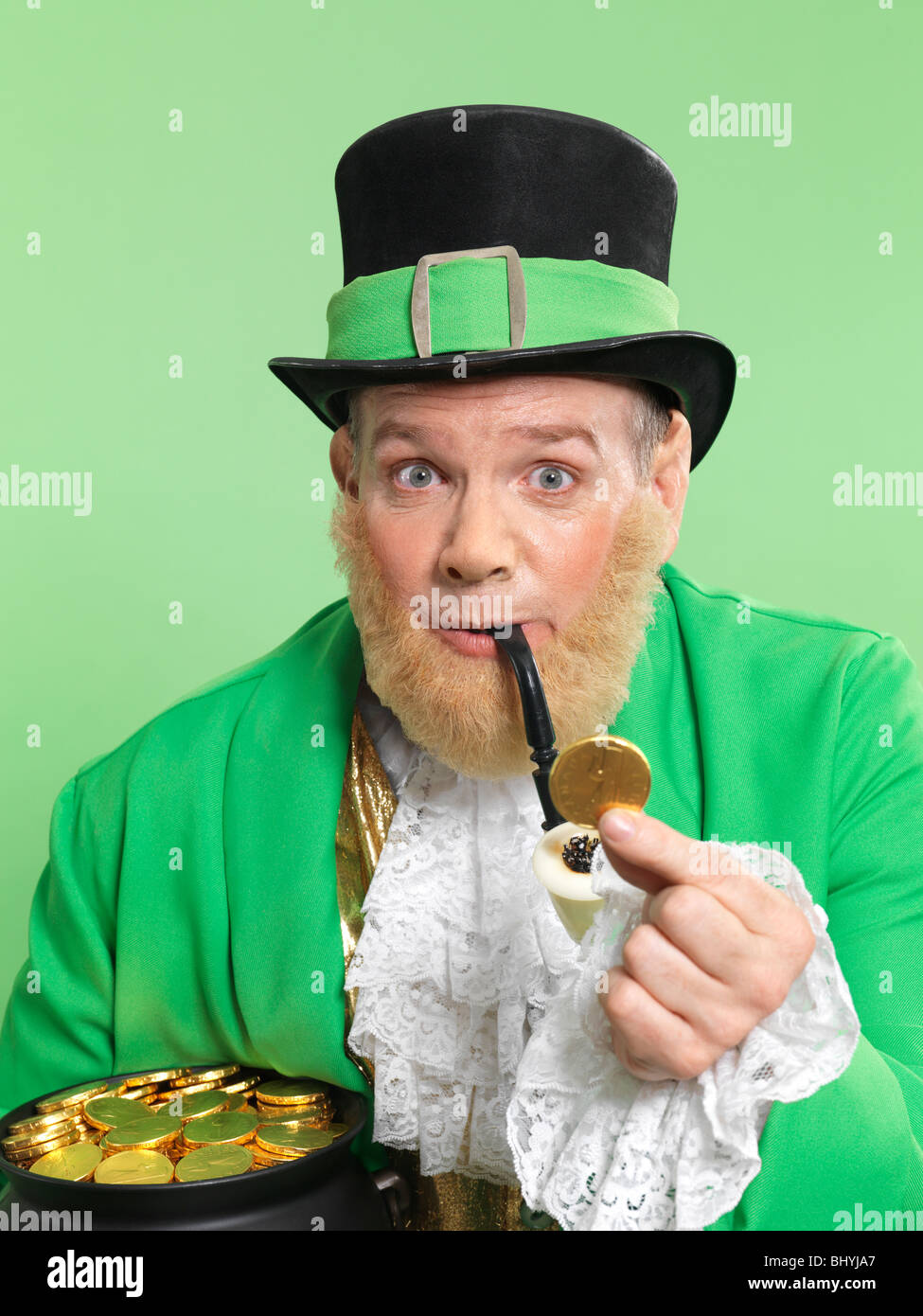 Leprechaun in bright green clothes holding a golden coin in his hand Stock Photo