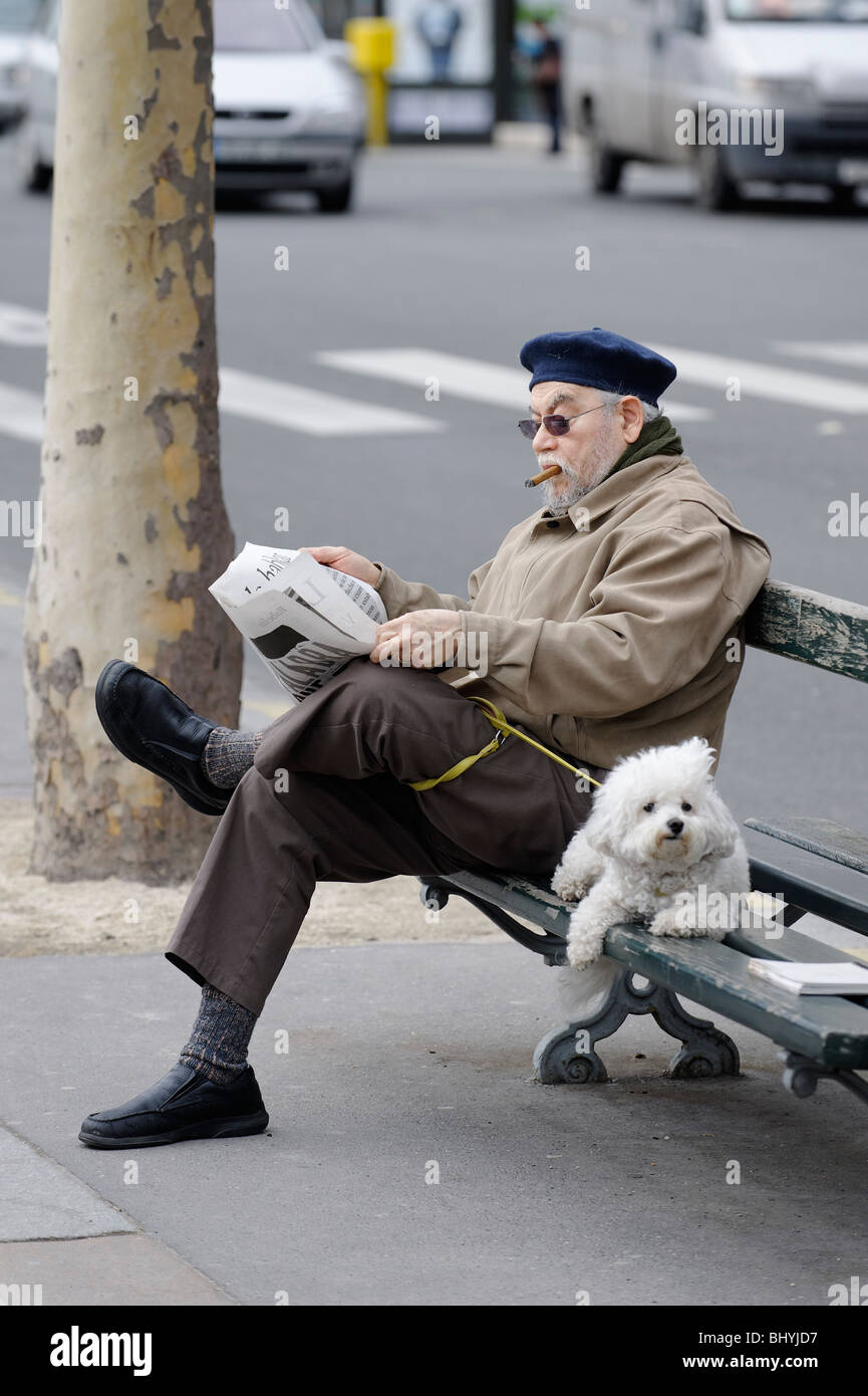 A man in traditional French beret and cigar reading the paper with a dog on a Paris street bench. - Stock Image