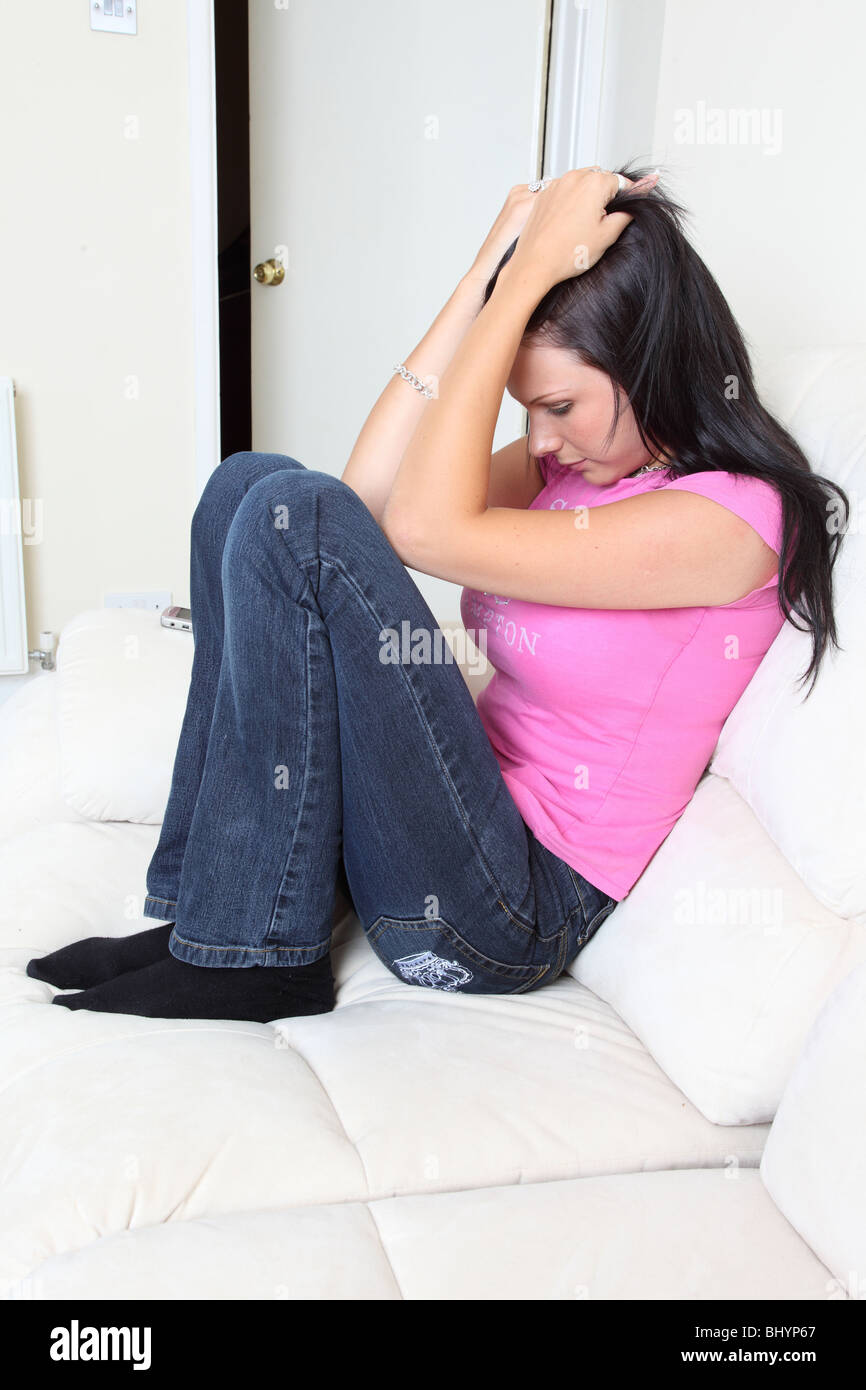 Attractive young woman sitting with her head in her hands looking upset and distressed, the door is slightly open - Stock Image