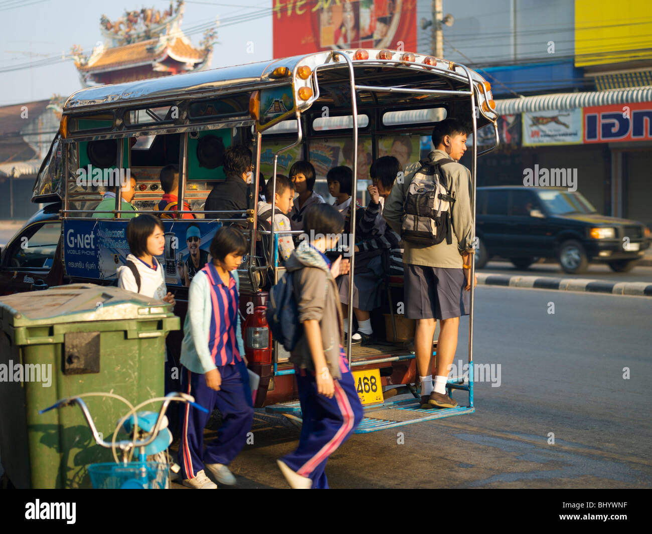 School children in udon thani thailand boarding a Songthaew taxi bus - Stock Image