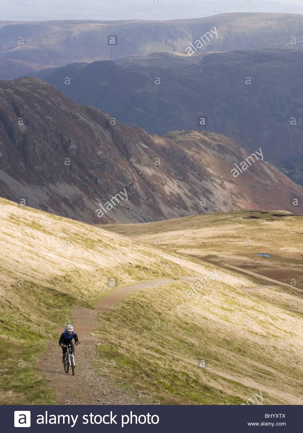 Mountain Biker climbing up a bridleway on Helvellyn, Cumbria. - Stock Image