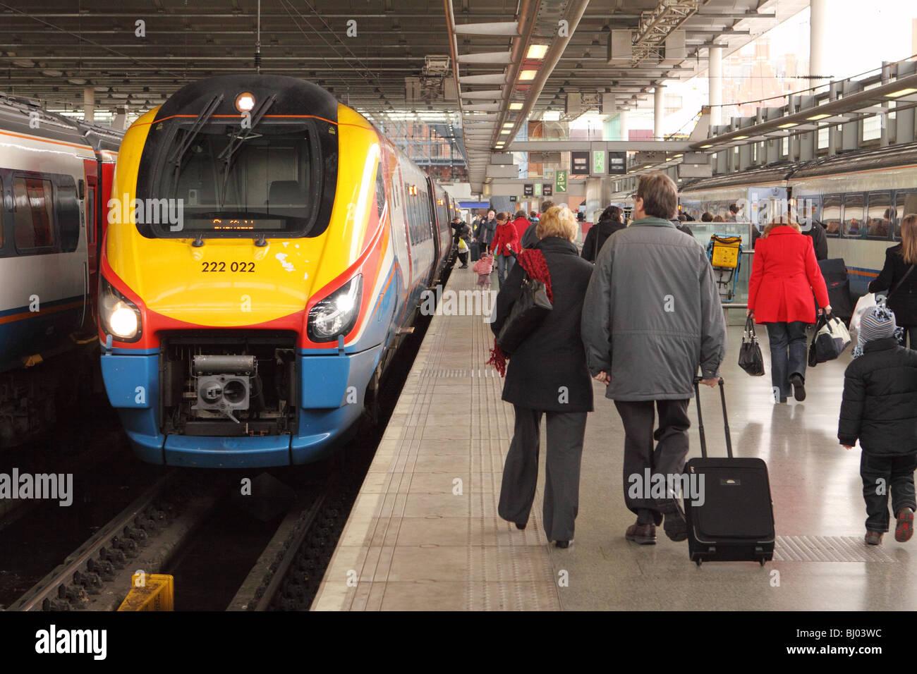 St Pancras railway station London passengers walk past an East Midlands Trains Class 222 Meridian train - Stock Image