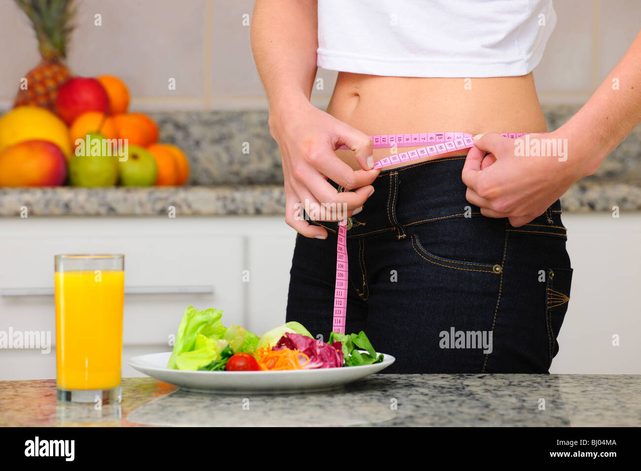 woman measuring her waist with a tape measure - Stock Image