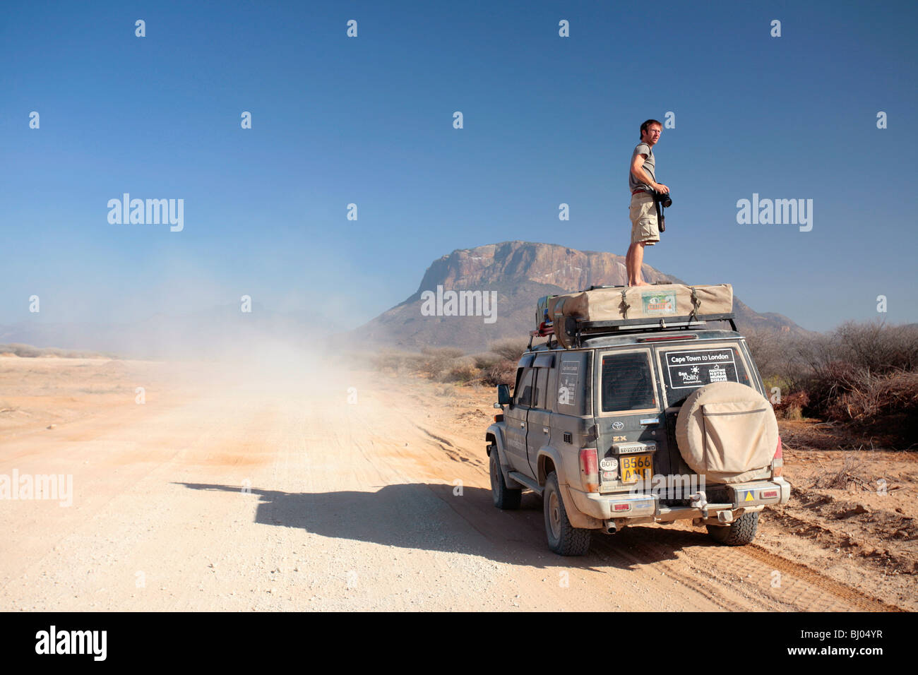 Man on the foor of an all terrain vehicle in Northern Kenya as another vehicle goes past - Stock Image