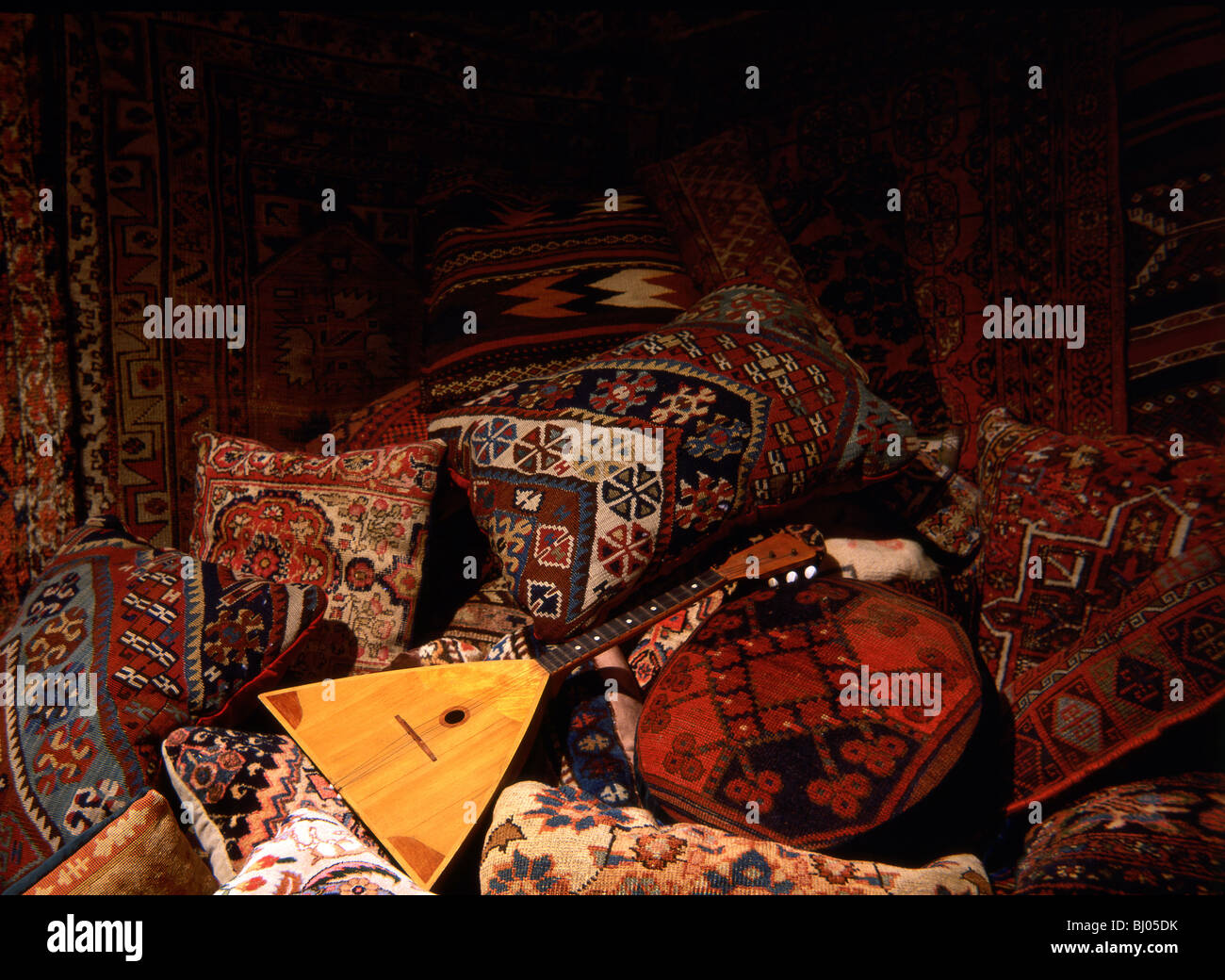 Oriental rugs and pillows with balalaika - Stock Image