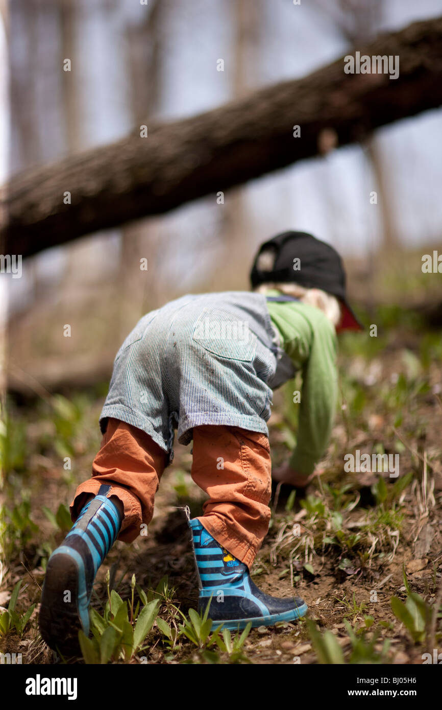 Young boy wearing rubber boots climbing up a hill in the woods. - Stock Image