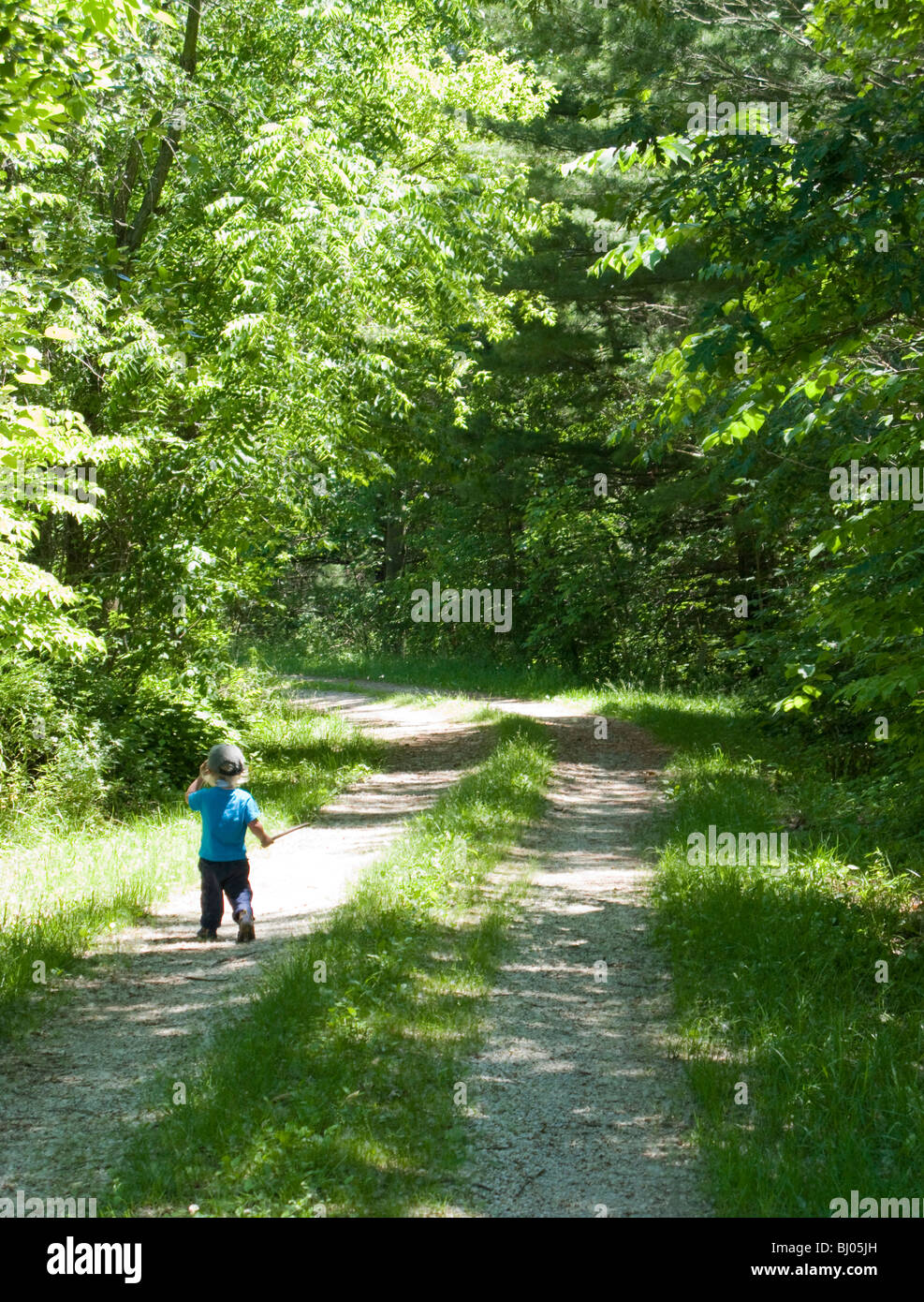Young boy walking down a gravel road holding a stick. - Stock Image