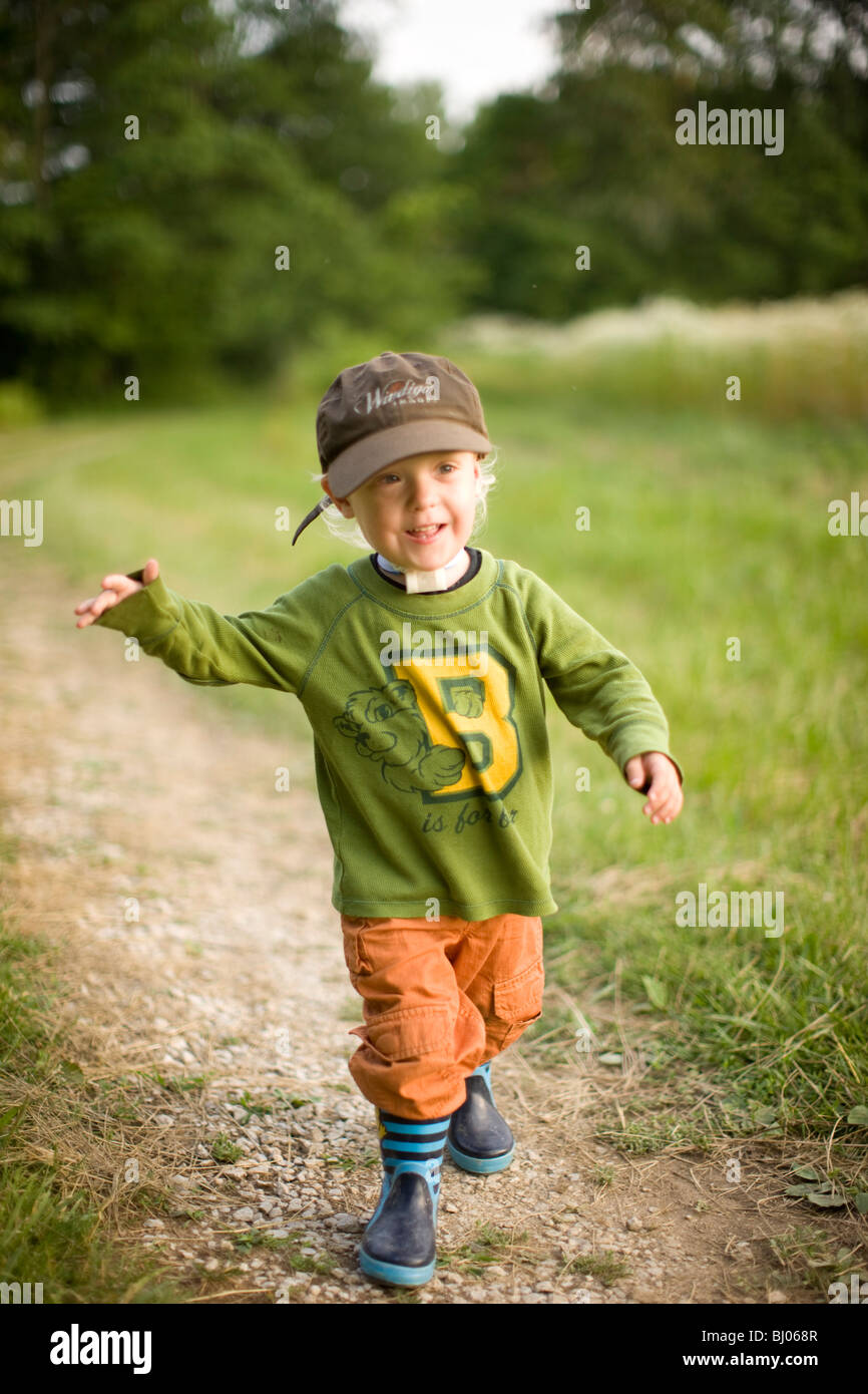 Young boy running on a gravel road. Stock Photo