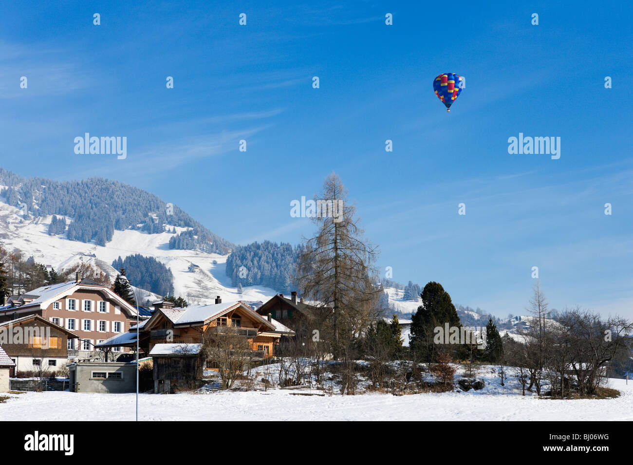 Single hot air balloon over the town during the January Balloon Festival, Chateau d'Oex, Vaud, Switzerland Stock Photo