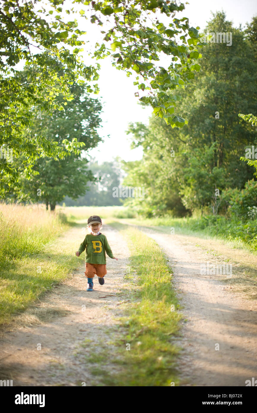 Young boy standing on a gravel road. Stock Photo