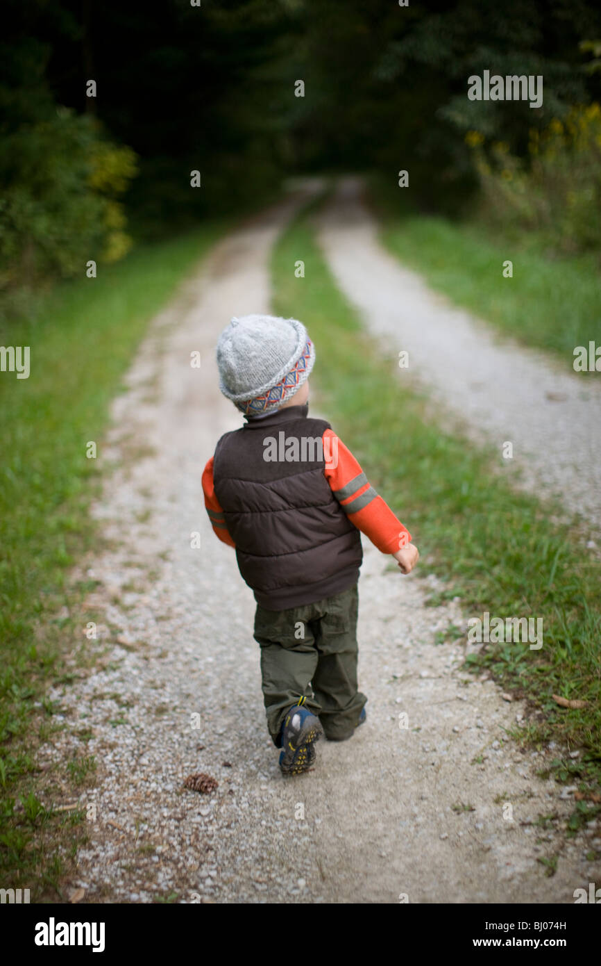 Young boy walking down a gravel road. - Stock Image