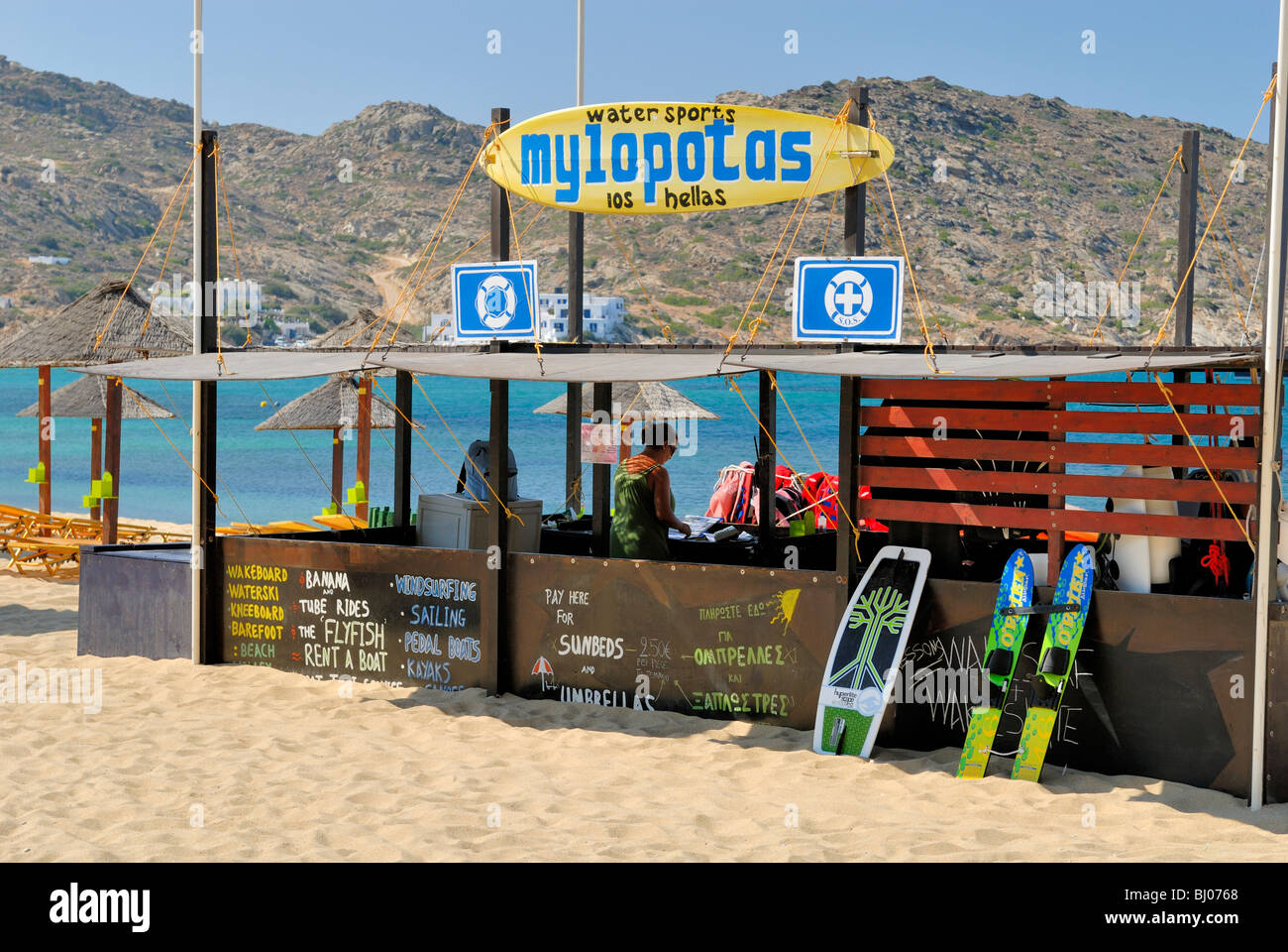 The Mylopotas Water Sport Center and the Mylopotas beach. Mylopotas Village, Ios Island, Cyclades Islands, Greece, - Stock Image